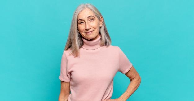 Vrouw van middelbare leeftijd glimlachend gelukkig met een hand op de heup en zelfverzekerde, positieve, trotse en vriendelijke houding