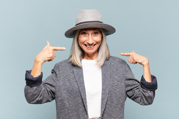 Vrouw van middelbare leeftijd glimlachend vol vertrouwen wijzend op een eigen brede glimlach, positieve, ontspannen, tevreden houding