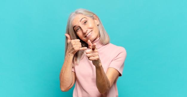 Vrouw van middelbare leeftijd glimlachend vrolijk en wijzend naar de camera tijdens het maken van een bel je later gebaar, praten over de telefoon