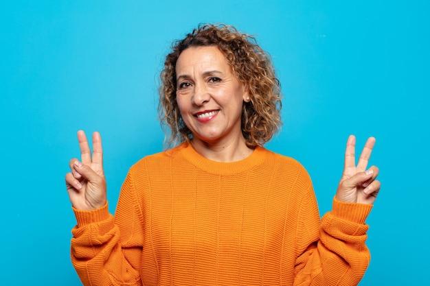 Vrouw van middelbare leeftijd glimlachte en kijkt gelukkig, vriendelijk en tevreden, gebarend met beide handen naar overwinning of vrede