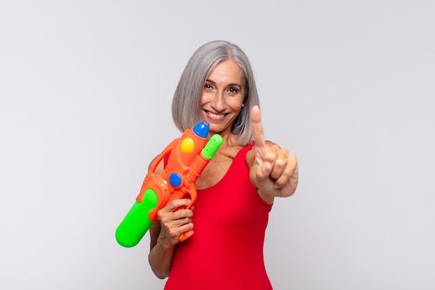 Vrouw van middelbare leeftijd glimlachte trots en zelfverzekerd nummer één triomfantelijk poseert, zich als een leider met een waterpistool