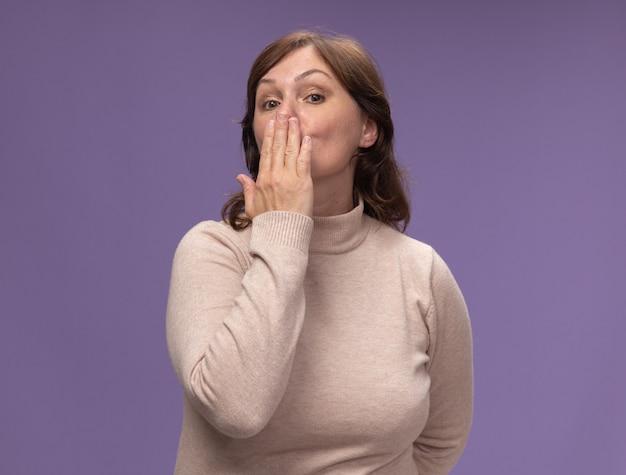 Vrouw van middelbare leeftijd in beige coltrui die een kus blaast die zich over purpere muur bevindt