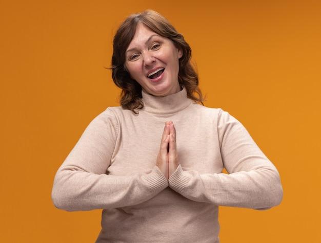 Vrouw van middelbare leeftijd in beige coltrui hand in hand als namaste glimlachend vriendelijk staande over oranje muur