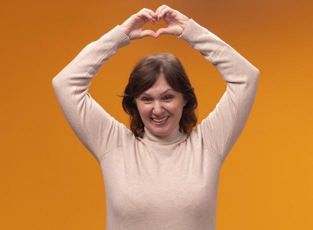 Vrouw van middelbare leeftijd in beige coltrui hart gebaar maken boven haar hoofd glimlachend vrolijk staande over oranje muur
