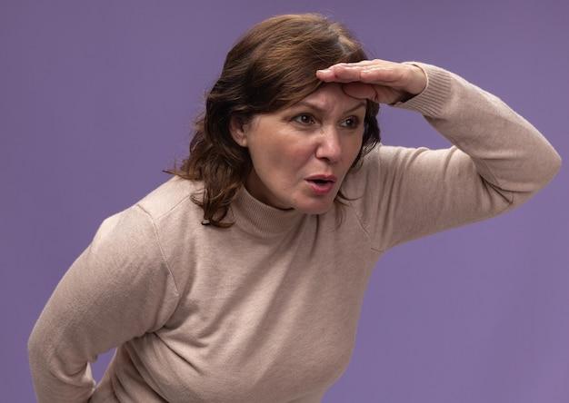 Vrouw van middelbare leeftijd in beige coltrui op zoek ver weg met hand boven het hoofd staande over paarse muur