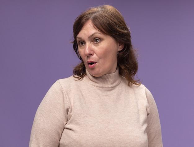 Vrouw van middelbare leeftijd in beige coltrui opzij kijken verward en verrast staande over paarse muur