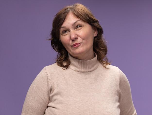 Vrouw van middelbare leeftijd in beige coltrui opzoeken ontevreden staande over paarse muur