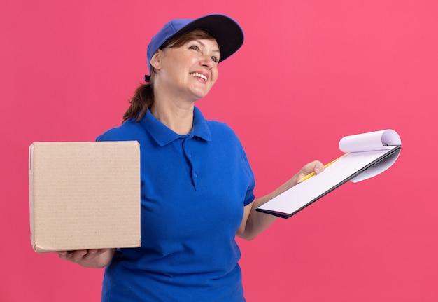 Vrouw van middelbare leeftijd in blauw uniform en pet met kartonnen doos en klembord met blanco pagina's opzoeken met glimlach op gezicht staande over roze muur