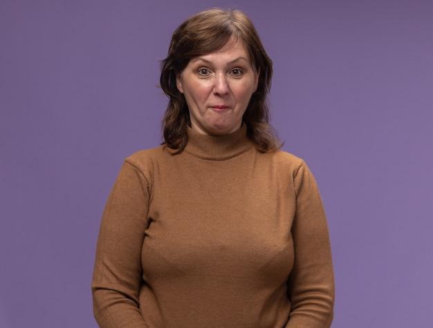 Vrouw van middelbare leeftijd in bruine coltrui die verward en verbaasd zich over purpere muur bevindt