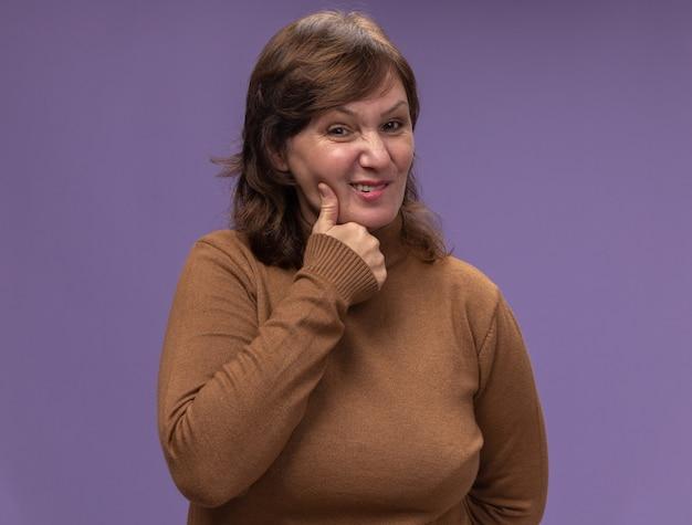Vrouw van middelbare leeftijd in bruine coltrui die verward kijkt wat betreft haar wang met kiespijn die zich over paarse muur bevindt