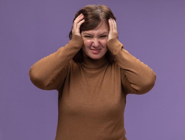 Vrouw van middelbare leeftijd in bruine coltrui op zoek gefrustreerd en verward met handen op haar hoofd staande over paarse muur