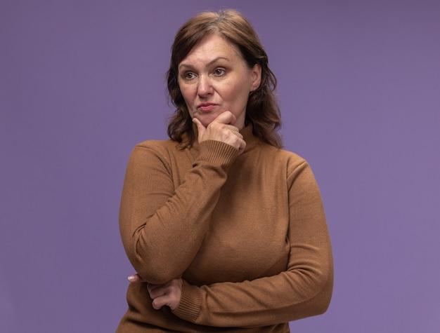 Vrouw van middelbare leeftijd in bruine coltrui opzij kijken met ernstig gezicht met hand op kin denken staande over paarse muur