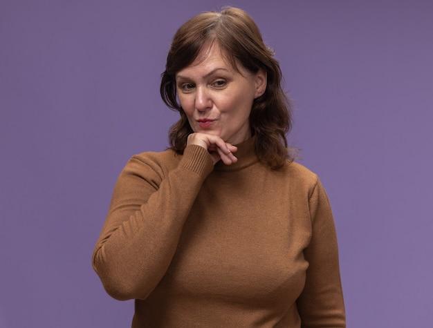 Vrouw van middelbare leeftijd in bruine coltrui opzij kijken met hand op kin positief denken staande over paarse muur