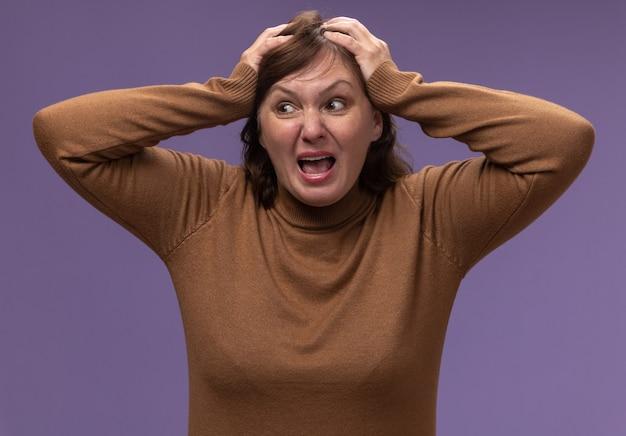 Vrouw van middelbare leeftijd in bruine coltrui schreeuwen wild trekken haar haren staande over paarse muur