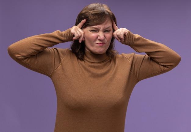 Vrouw van middelbare leeftijd in bruine coltrui wat betreft haar hoofd dat ontevreden is met sterke hoofdpijn die zich over paarse muur bevindt