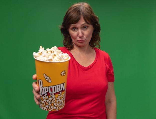 Vrouw van middelbare leeftijd in de rode emmer van de t-shirtholding met popcorn met droevige uitdrukking die zich over groene muur bevindt
