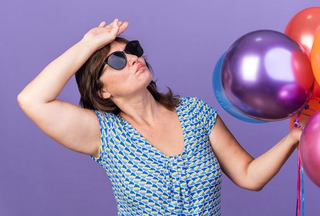 Vrouw van middelbare leeftijd in een bril met een stel kleurrijke ballonnen die moe en verveeld opkijkt met de hand op haar hoofd om een verjaardagsfeestje te vieren dat over de paarse muur staat