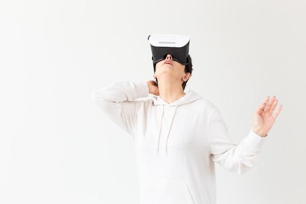 Vrouw van middelbare leeftijd in een witte trui kijken naar een film met een bril van virtual reality