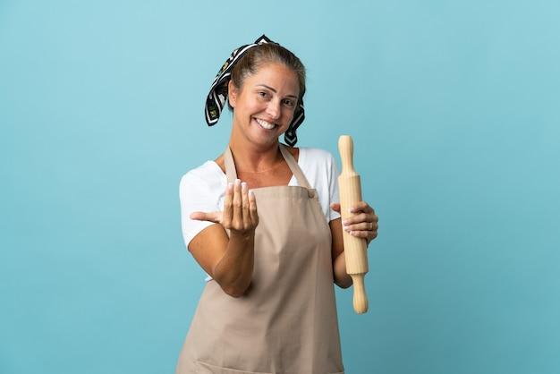Vrouw van middelbare leeftijd in eenvormige chef-kok die uitnodigt om met de hand te komen. blij dat je gekomen bent