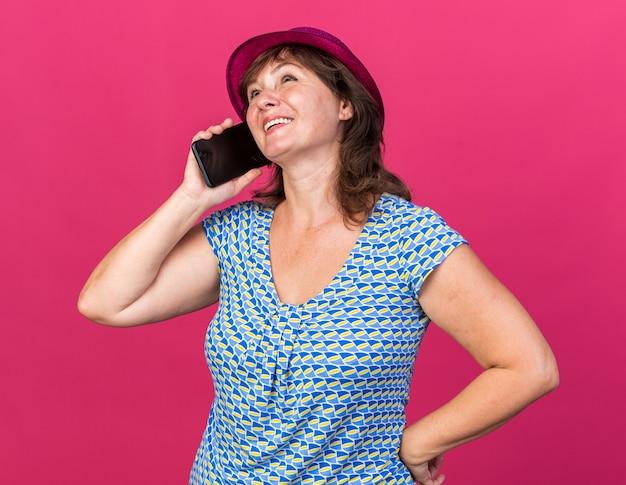 Vrouw van middelbare leeftijd in feestmuts blij en positief glimlachend vrolijk terwijl ze op mobiele telefoon praat om verjaardagsfeestje te vieren dat over roze muur staat
