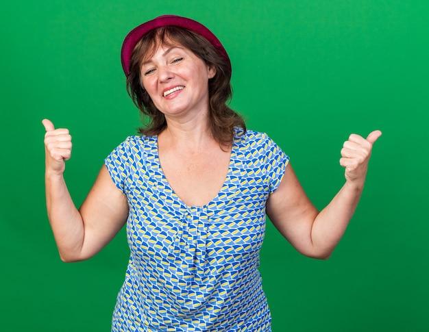 Vrouw van middelbare leeftijd in feestmuts, blij en vrolijk lachend en duimen omhoog om het verjaardagsfeestje te vieren dat over de groene muur staat