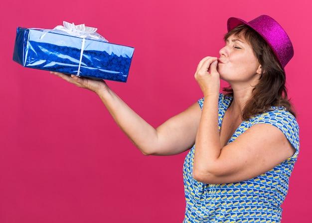 Vrouw van middelbare leeftijd in feestmuts die een cadeautje vasthoudt en ernaar kijkt en een heerlijk gebaar maakt met de hand die een verjaardagsfeestje viert dat over een roze muur staat