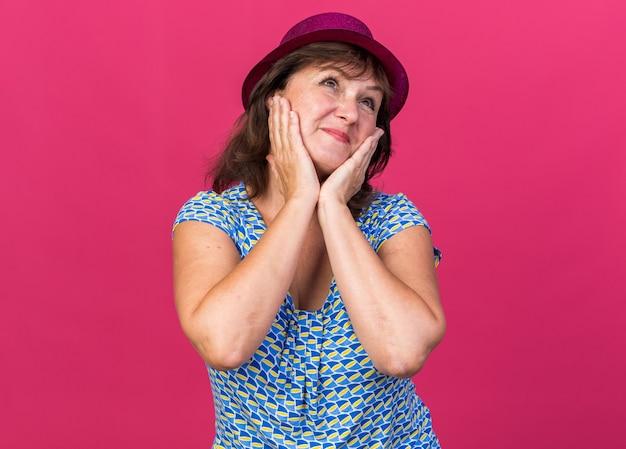 Vrouw van middelbare leeftijd in feestmuts die gelukkig en vrolijk glimlacht opkijkt
