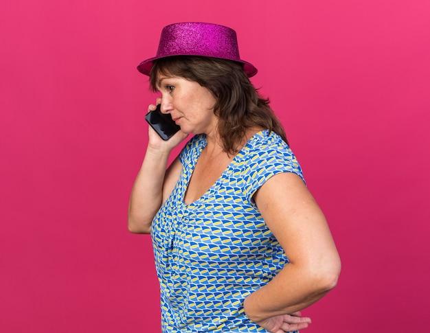 Vrouw van middelbare leeftijd in feestmuts die met een serieus gezicht op mobiele telefoon praat