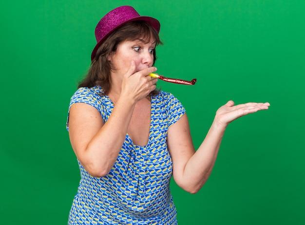 Vrouw van middelbare leeftijd in feestmuts die op een fluitje blaast, blij en vrolijk vierend verjaardagsfeestje dat over groene muur staat