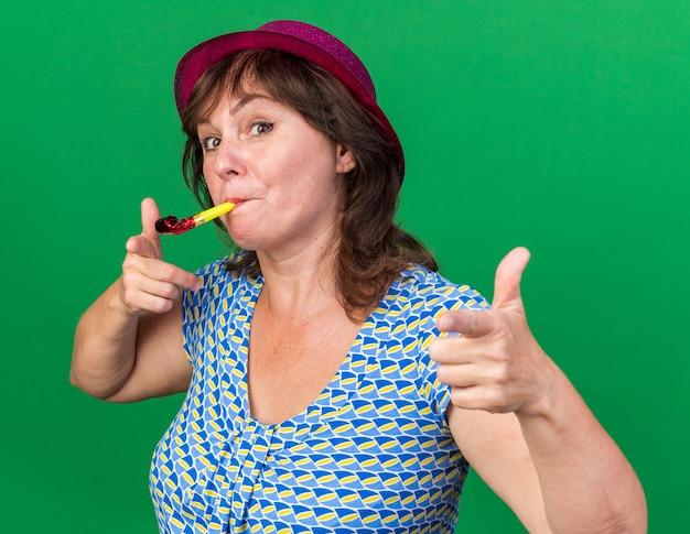 Vrouw van middelbare leeftijd in feestmuts die op een fluitje blaast, blij en vrolijk wijzend met wijsvingers naar de camera
