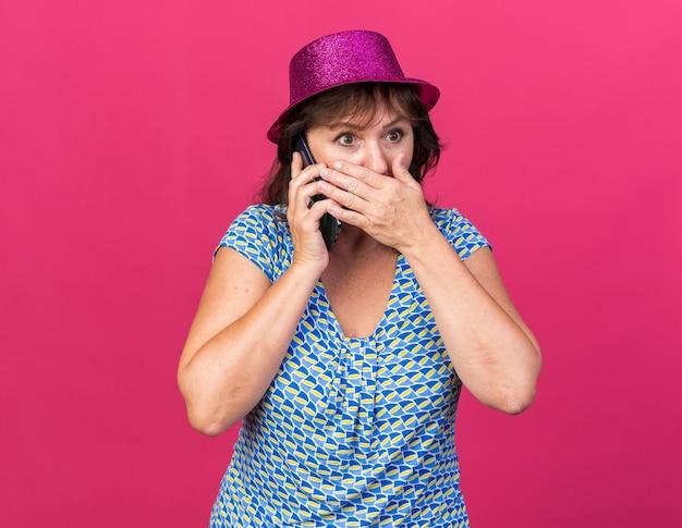 Vrouw van middelbare leeftijd in feestmuts die verbaasd kijkt terwijl ze de mond bedekt met de hand terwijl ze op een mobiele telefoon praat