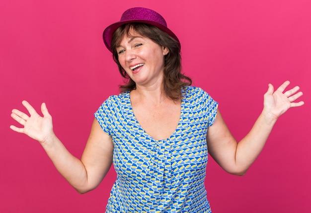 Vrouw van middelbare leeftijd in feestmuts die vrolijk lacht met opgeheven armen om verjaardagsfeestje te vieren dat over roze muur staat