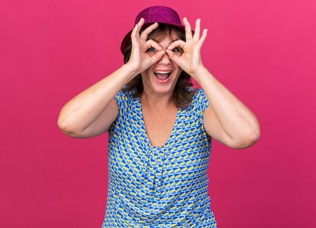 Vrouw van middelbare leeftijd in feestmuts door vingers die een verrekijker gebaar maken en vrolijk glimlachen?