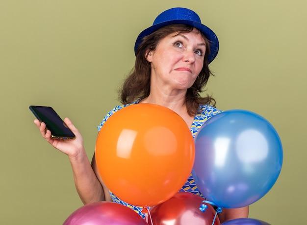 Vrouw van middelbare leeftijd in feestmuts met een bos kleurrijke ballonnen die een smartphone vasthoudt en verbaasd opkijkt