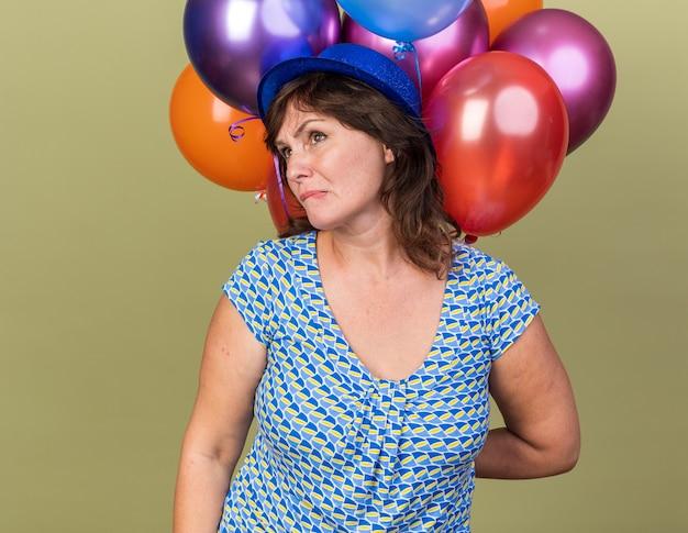 Vrouw van middelbare leeftijd in feestmuts met een bos kleurrijke ballonnen die opzij kijken en een wrange mond maken met een teleurgestelde uitdrukking die een verjaardagsfeestje viert dat zich over de groene muur bevindt