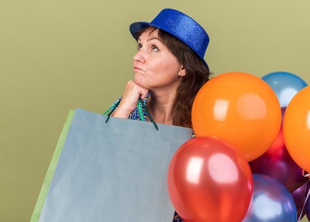 Vrouw van middelbare leeftijd in feestmuts met een bos kleurrijke ballonnen die papieren zakken vasthoudt en verbaasd opkijkt