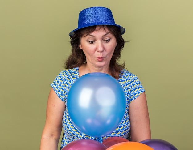 Vrouw van middelbare leeftijd in feestmuts met een bos kleurrijke ballonnen die verbaasd en verrast kijkt naar het vieren van een verjaardagsfeestje dat over de groene muur staat