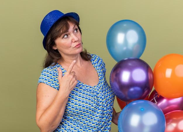 Vrouw van middelbare leeftijd in feestmuts met een bos kleurrijke ballonnen die verbaasd opkijkt om een verjaardagsfeestje te vieren dat over de groene muur staat
