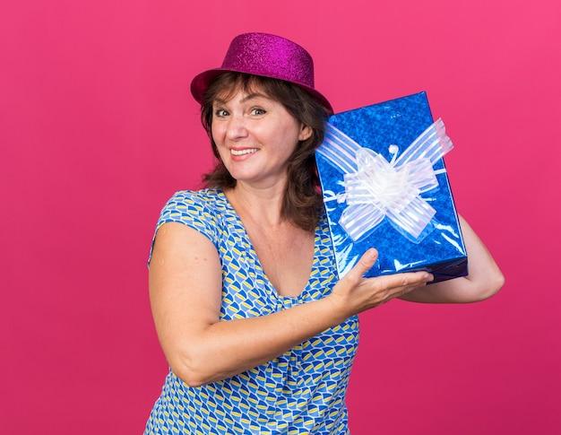 Vrouw van middelbare leeftijd in feestmuts met een cadeautje, blij en vrolijk glimlachend, breeduit vierend verjaardagsfeestje staande over roze muur
