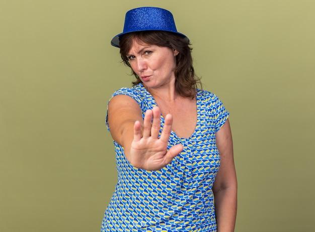 Vrouw van middelbare leeftijd in feestmuts met een serieus gezicht die een stopgebaar maakt met de hand die een verjaardagsfeestje viert dat over de groene muur staat