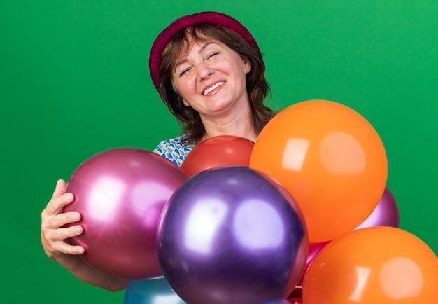 Vrouw van middelbare leeftijd in feestmuts met kleurrijke ballonnen, blij en verheugd om het verjaardagsfeestje te vieren dat over de groene muur staat
