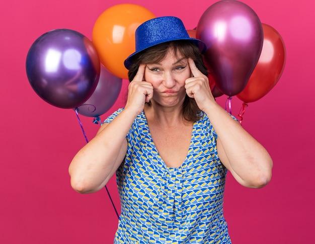 Vrouw van middelbare leeftijd in feestmuts met kleurrijke ballonnen die de hoeken van haar ogen naar de zijkanten trekt, verward en ontevreden verjaardagsfeestje vieren dat over roze muur staat