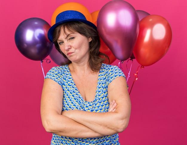 Vrouw van middelbare leeftijd in feestmuts met kleurrijke ballonnen die ontevreden is met gekruiste armen om verjaardagsfeestje te vieren dat over roze muur staat