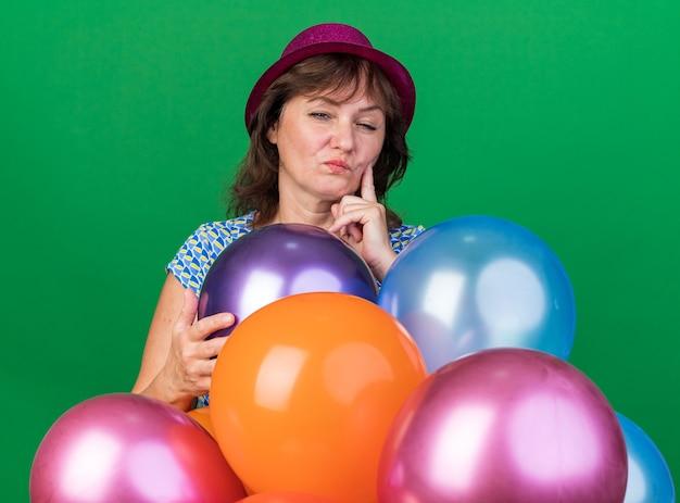 Vrouw van middelbare leeftijd in feestmuts met kleurrijke ballonnen met een sceptische uitdrukking die een verjaardagsfeestje viert dat over de groene muur staat