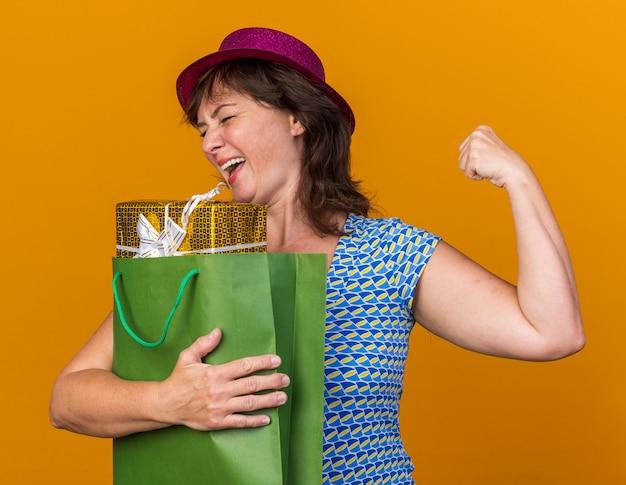Vrouw van middelbare leeftijd in feestmuts met papieren zak met verjaardagscadeaus blij en opgewonden gebalde vuist