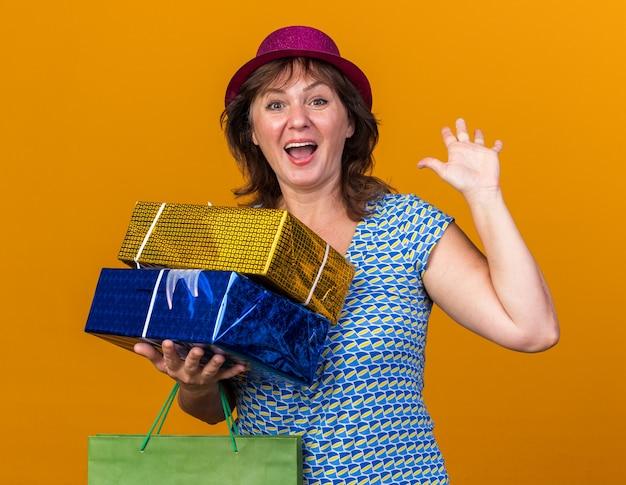 Vrouw van middelbare leeftijd in feestmuts met papieren zak met verjaardagscadeaus blij en vrolijk glimlachend met opgeheven arm