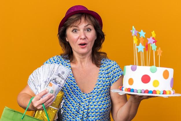 Vrouw van middelbare leeftijd in feestmuts met papieren zak met verjaardagscadeaus en cake verbaasd en verrast om verjaardagsfeestje te vieren dat over oranje muur staat