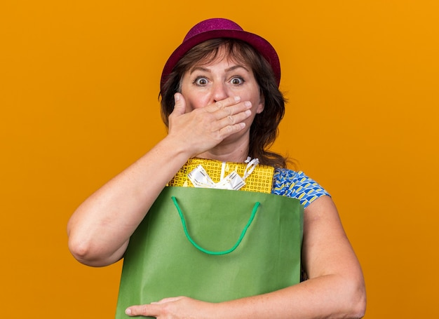 Vrouw van middelbare leeftijd in feestmuts met papieren zak met verjaardagscadeaus, geschokt die mond bedekt met hand