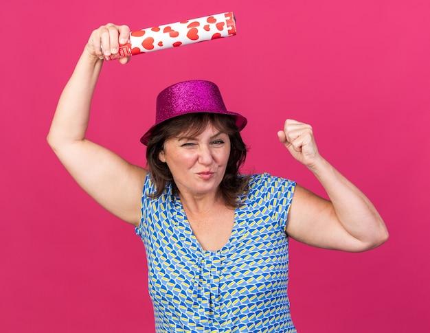 Vrouw van middelbare leeftijd in feestmuts met petard blij en opgewonden balde vuist vieren verjaardagsfeestje staande over roze muur