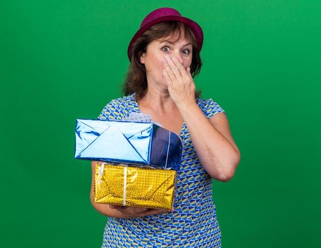 Vrouw van middelbare leeftijd in feestmuts met verjaardagscadeautjes die geschokt zijn mond met hand bedekken